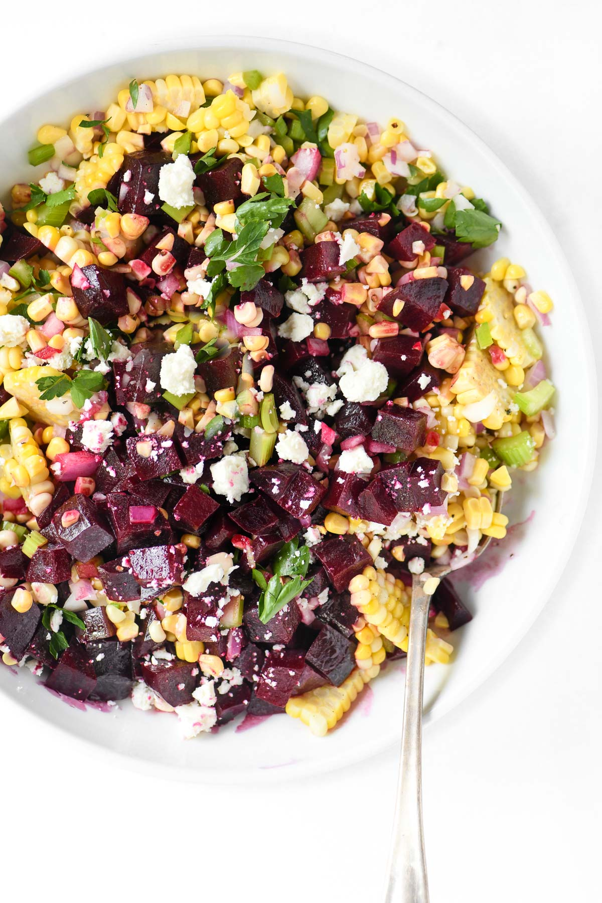 beet and corn salad in bowl with spoon