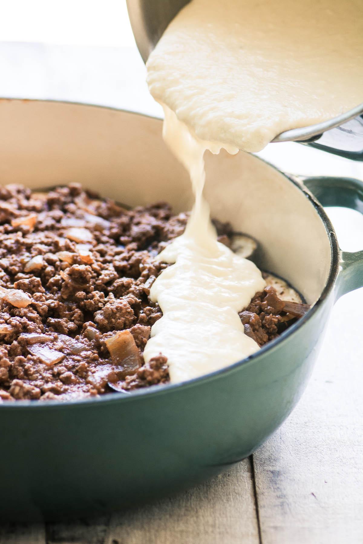 Pouring bechamel sauce over a Moussaka casserole