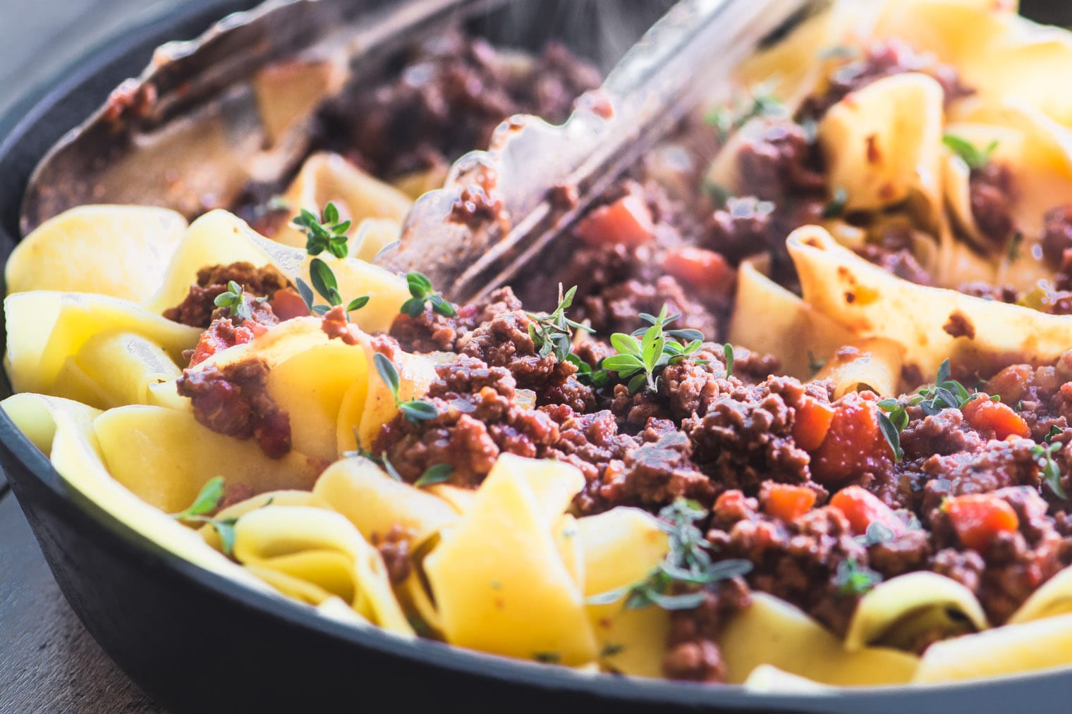 pasta with Italian meat sauce in skillet with tongs