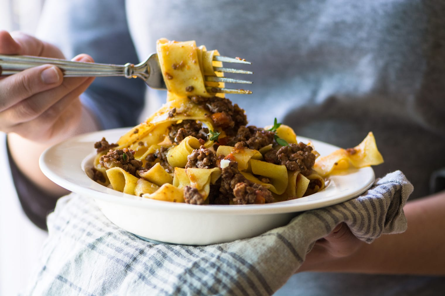 taking forkful of pasta Bolognese