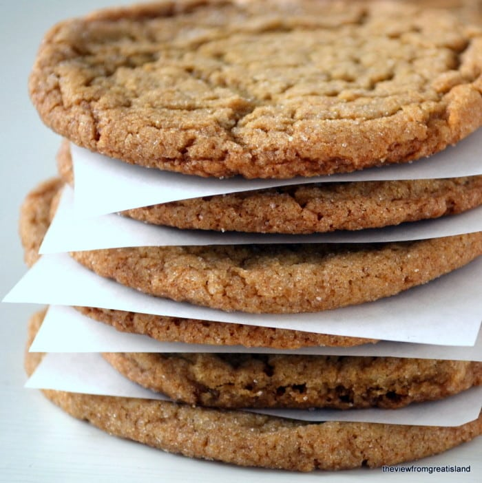 a stack of chewy ginger cookies with parchment paper dividers