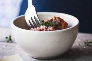 taking a bite of meatballs al forno