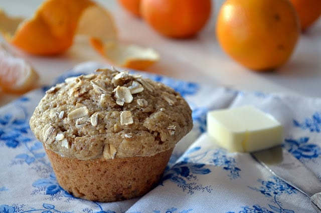 An Orange Walnut Oat Bran Muffins with butter and oranges