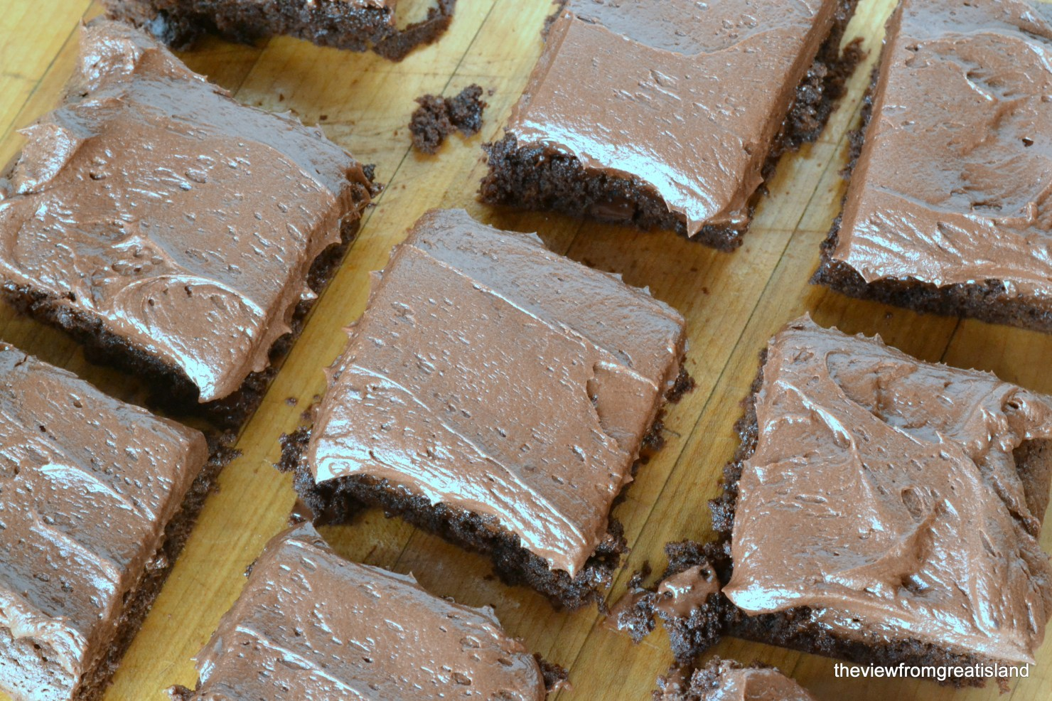 Chocolate Fudge Brownies with Chocolate Buttercream on a wooden cutting board