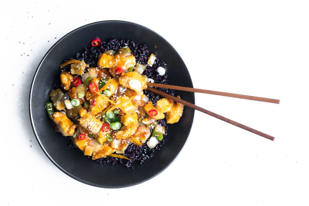 tangerine chicken in a black bowl with chopsticks