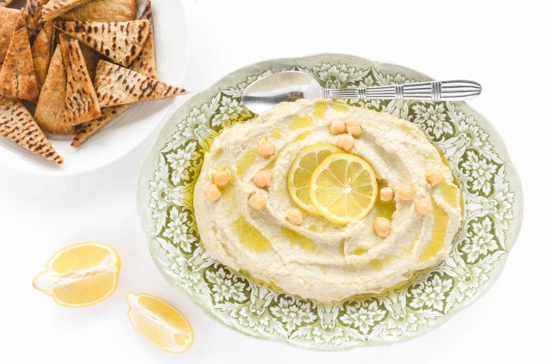 lemon artichoke hummus on a platter with pita chips