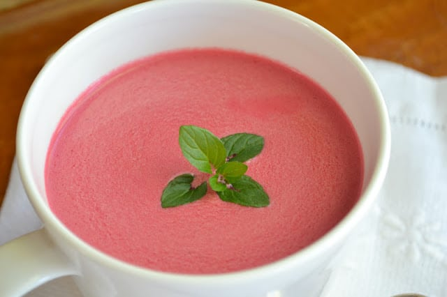 chilled beet soup in a white mug, with mint sprig
