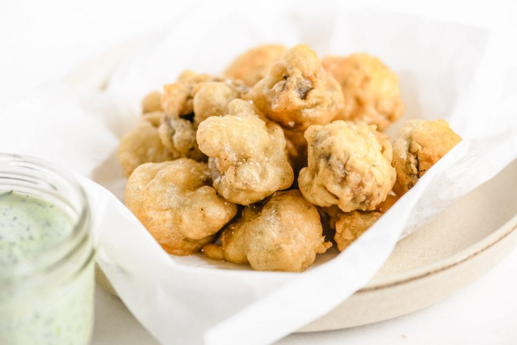 a plate of fried mushrooms with dip