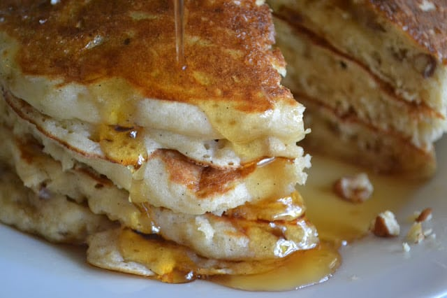 A stack of banana buttermilk pancakes with dripping syrup