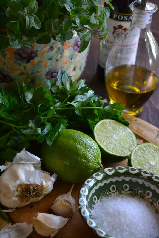 Photo of herbs, lime, garlic, oil, and salt for chimichurri sauce