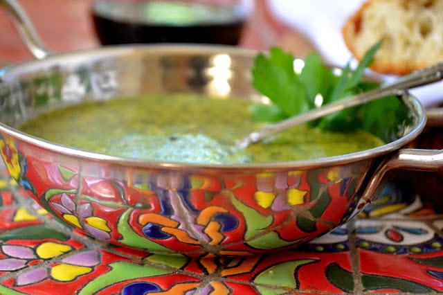 Side view of a bowl of chimichurri sauce garnished with cilantro.