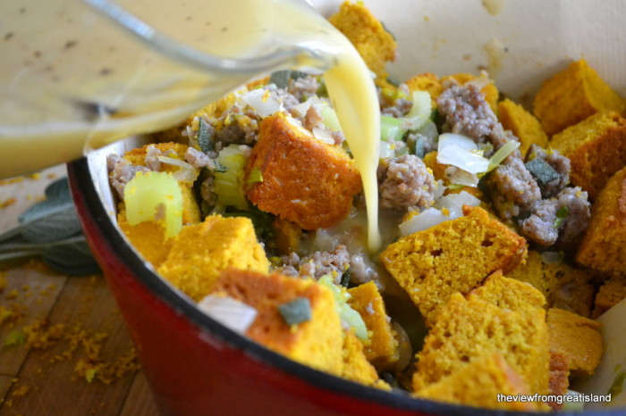 Pouring liquid ingredients into cornbread and sausage mixture.