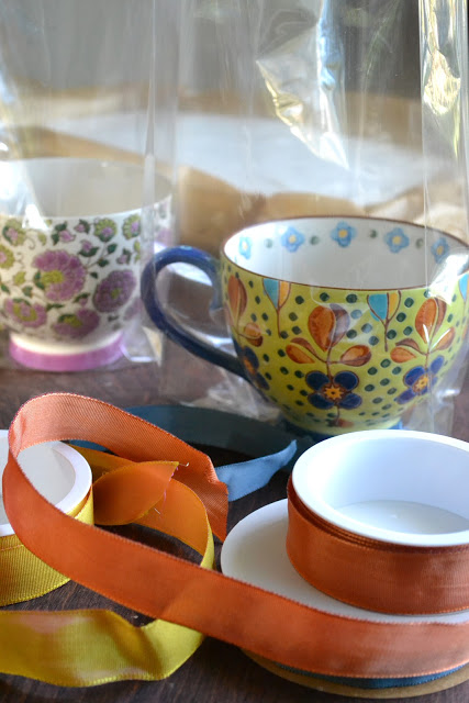 Wrapping Homemade Vanilla Bean Marshmallows in decorative mugs with cellophane and ribbons
