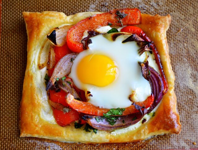 Overhead photo of a red pepper and baked egg galette on a baking tray.