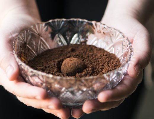 hands holding a glass bowl with cocoa powder and a chocolate truffle