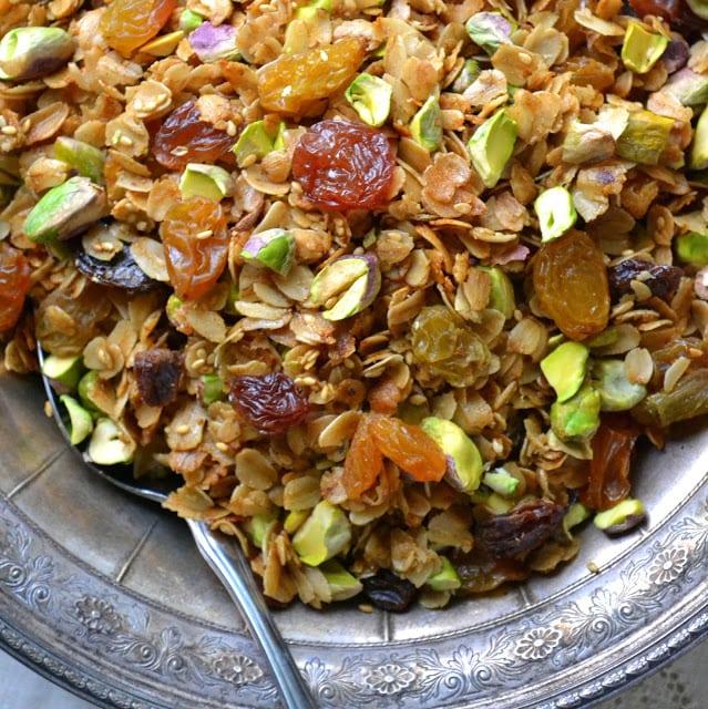 pistachio cardamom granola in a silver bowl with spoon