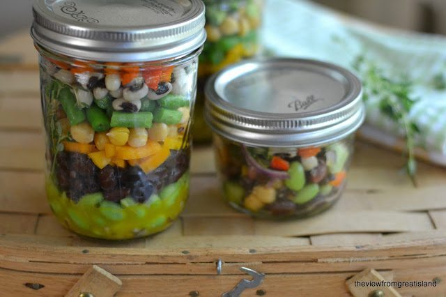 Photo of two jars of Mason Jar 7 Bean Salad on a wood surface.