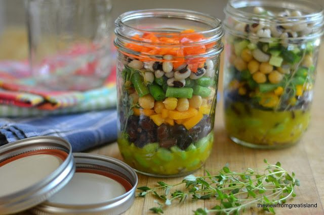 Photo of two jars of Mason Jar 7 Bean Salad with lids and thyme on a wood surface.