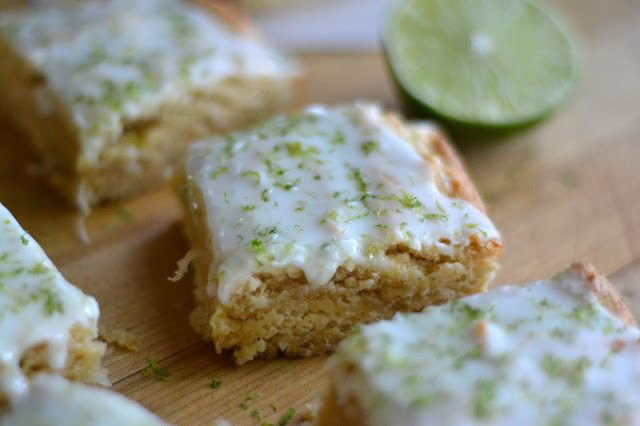 Photo of coconut lime squares on a wood surface.