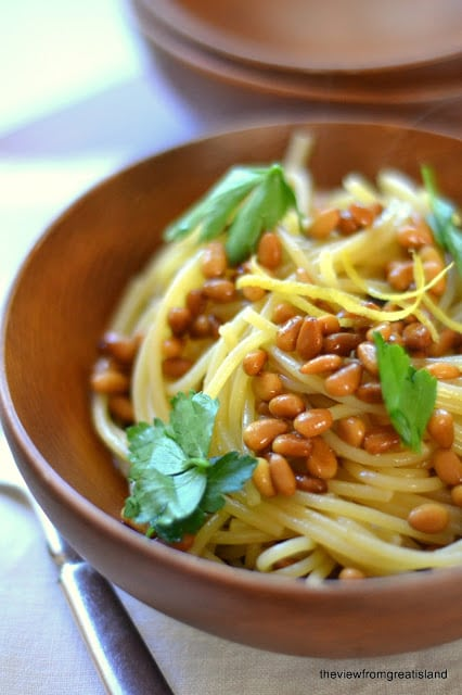 Spaghetti with roasted pin nuts in a wooden bowl