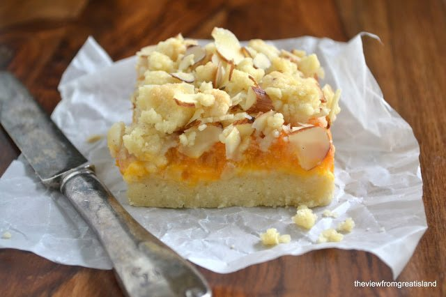 Photo of a Apricot Frangipane Crumble Bar on a piece of parchment paper with a knife against a wood background.