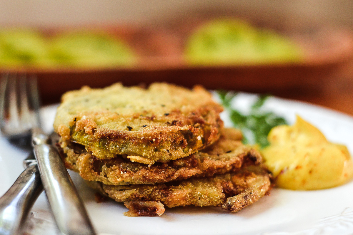 A stack of fried green tomatoes on a plate with cutlery