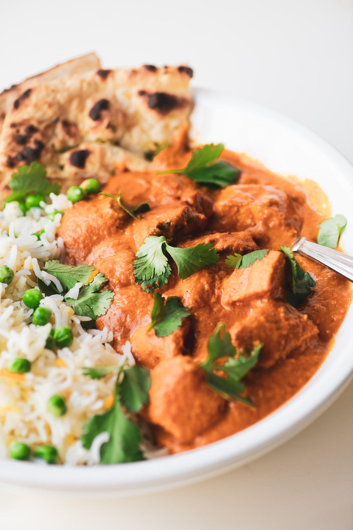chicken tikka masala in a bowl with rice and naan bread