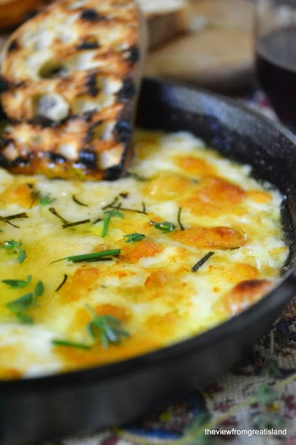 Baked cheese in a cast iron dish with a slice of bread dipped in.