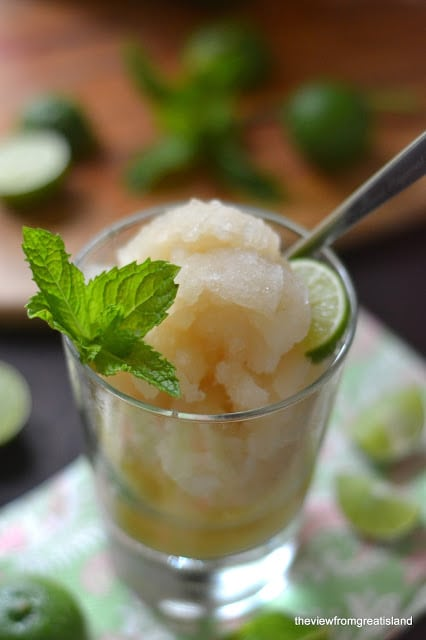 dirty mojito slushie in a glass with spoon and fresh mint