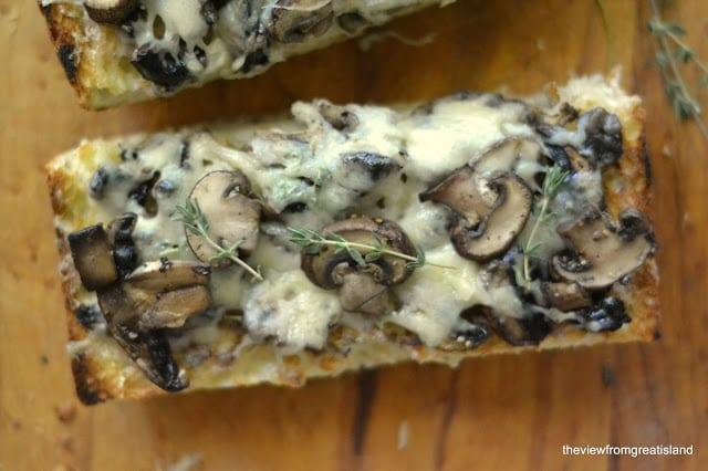 A slice of mushroom and Gruyere bruschetta with fresh thyme