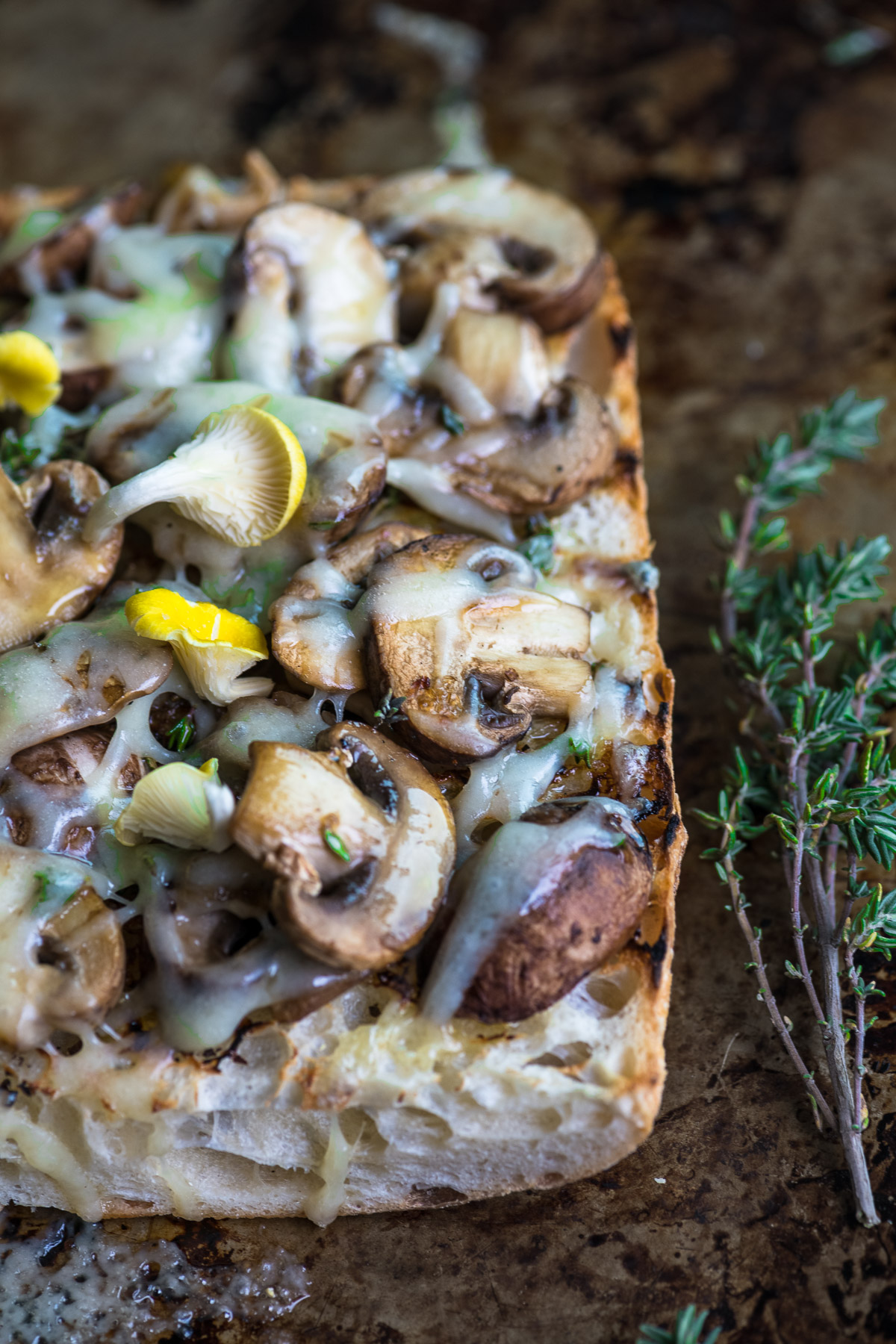 a mushroom and cheese bruschetta on a baking sheet with fresh thyme