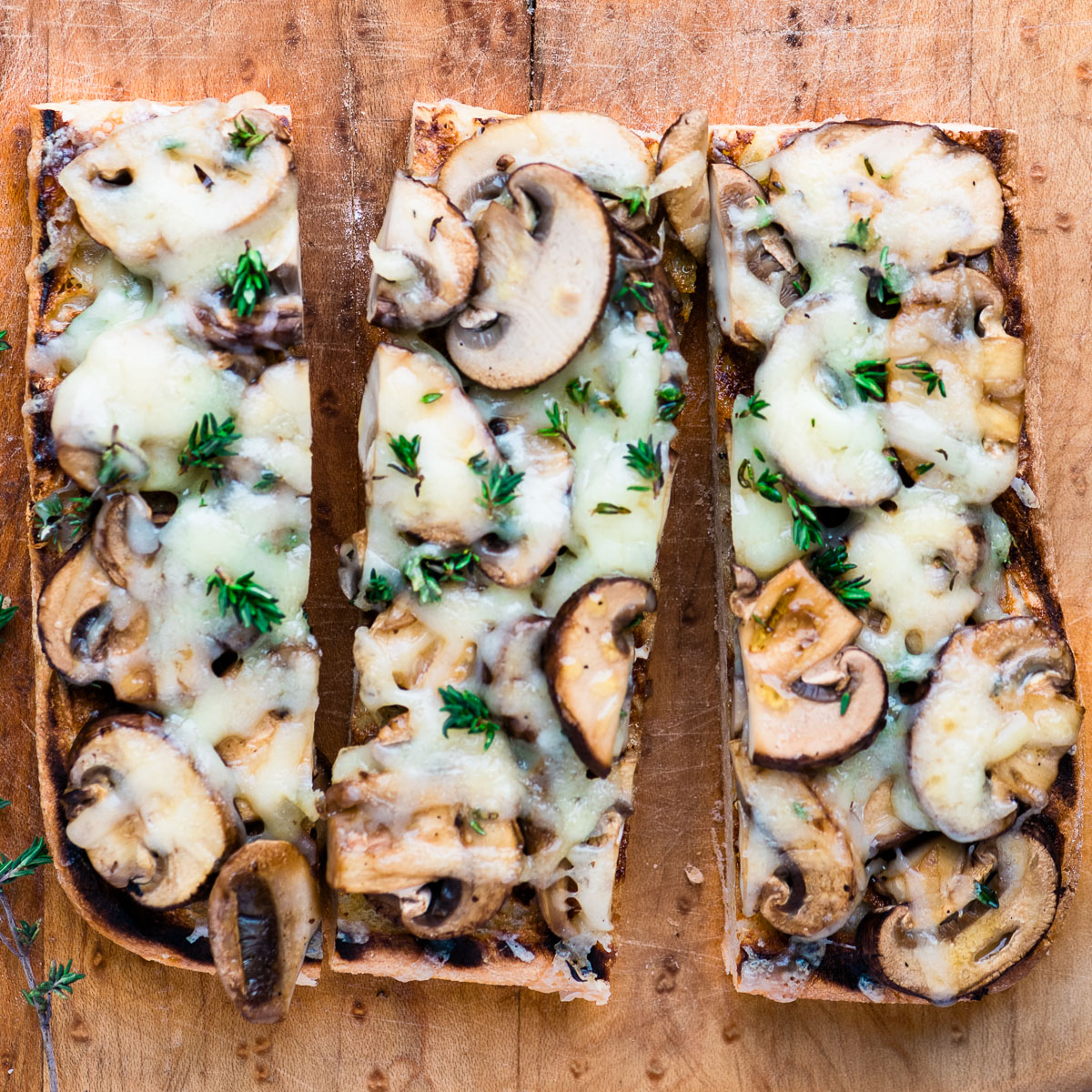 Slices of mushroom bruschetta on a wooden board