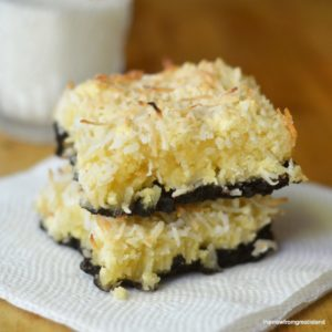Close up photo of two Black Bottom Coconut Squares on a napkin with a glass of milk in the background.