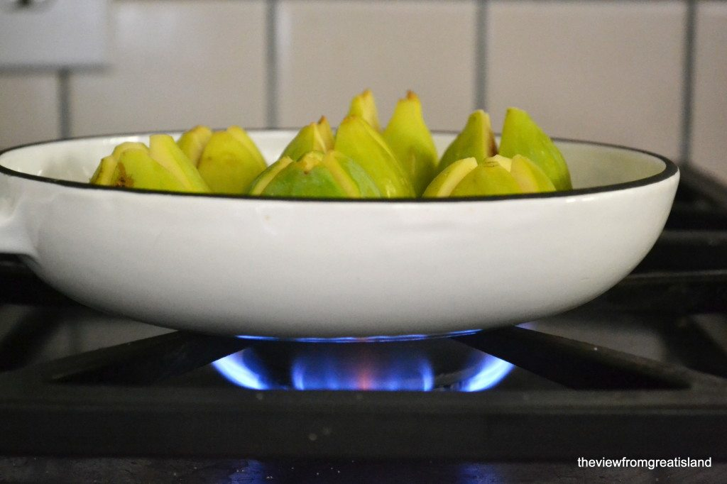 Side view photo of cardamom and brandy poached figs in a white pan on the stove.