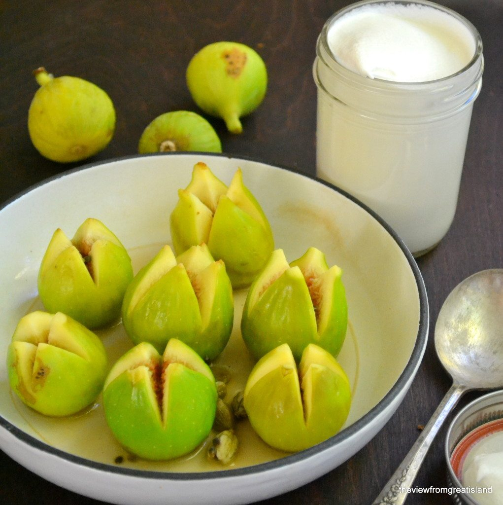 Photo of figs for cardamom and brandy poached figs in a white pan, with a jar of whipped cream and some more figs in the background.