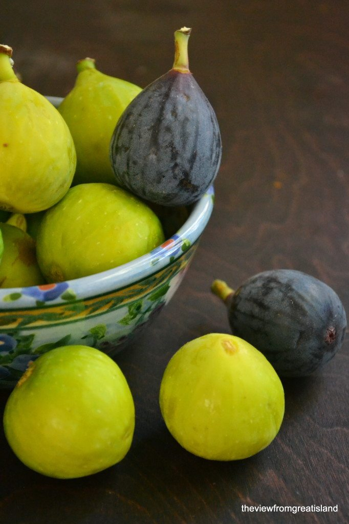 Photo of a bowl of figs against a dark wood background, with three figs in front of the bowl.