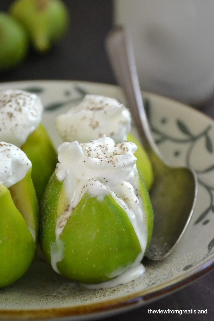 Photo of cardamom and brandy poached figs topped with whipped cream in a bowl with a spoon.