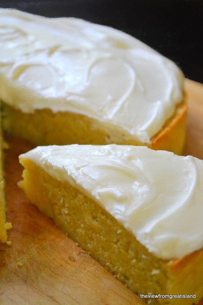Photo of flourless whole meyer lemon cake with a slice partially removed.