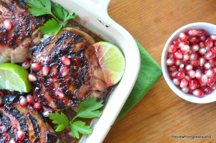 a pan of pomegranate and lime glazed chicken thighs with pomegranate seeds