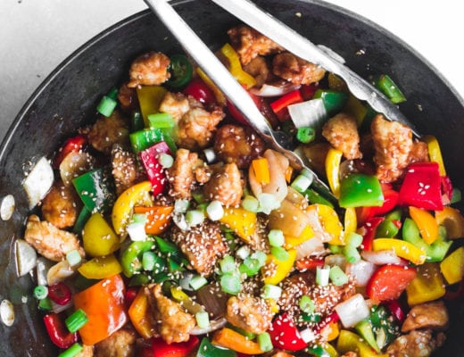 Colorful Firecracker Chicken in a wok with tongs