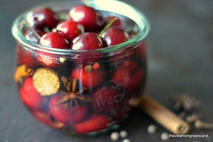Spiced Cocktail Cherries in a mason jar with cinnamon stick