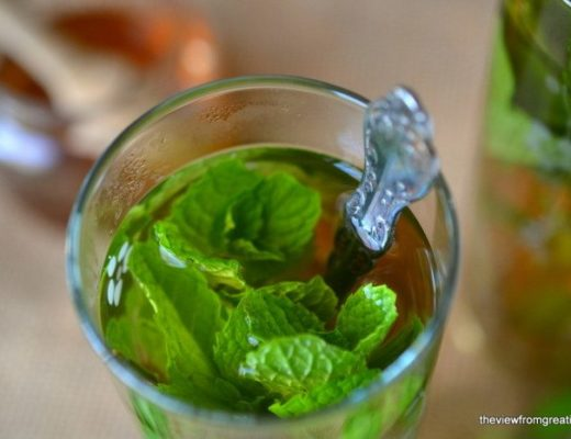 Photo of a glass of Sweet Moroccan Mint Tea with mint leaves and a spoon.