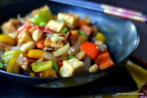 Kung Pao Tofu in a black bowl
