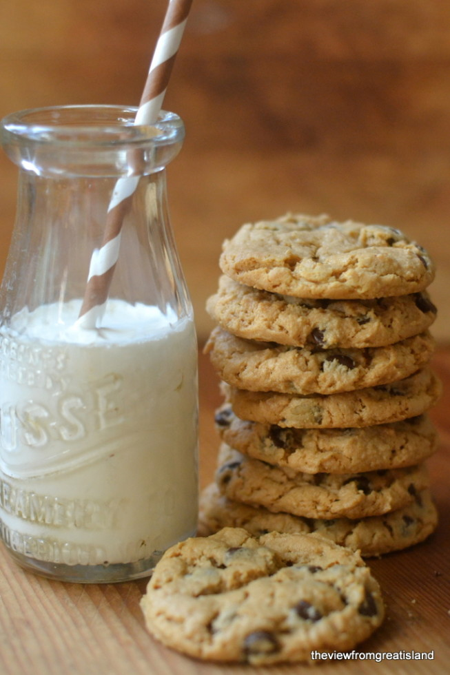 flourless cashew butter chocolate chip cookies stacked up with milk and a straw