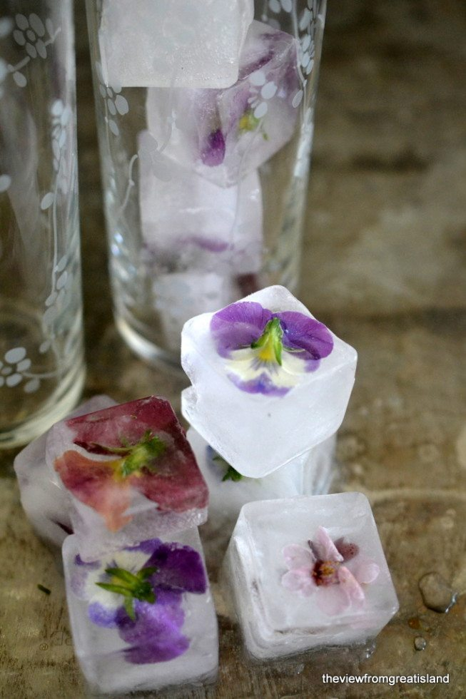 Photo of Edible Flower Ice Cubes on a wood surface with drinking glasses in the background.
