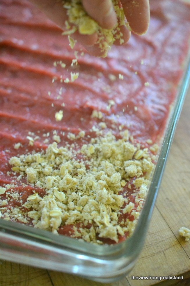 Photo of crumb topping being sprinkled on a tray of rhubarb crumb bars.