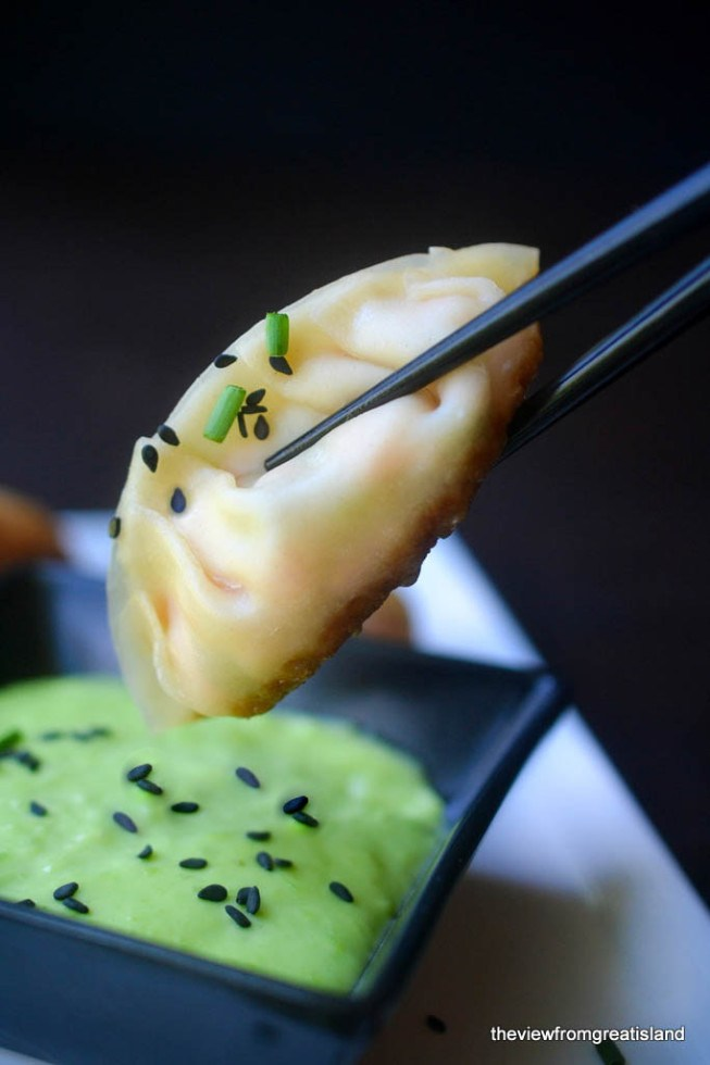 Dipping a homemade Salmon Potsticker into wasabi sauce with chopsticks
