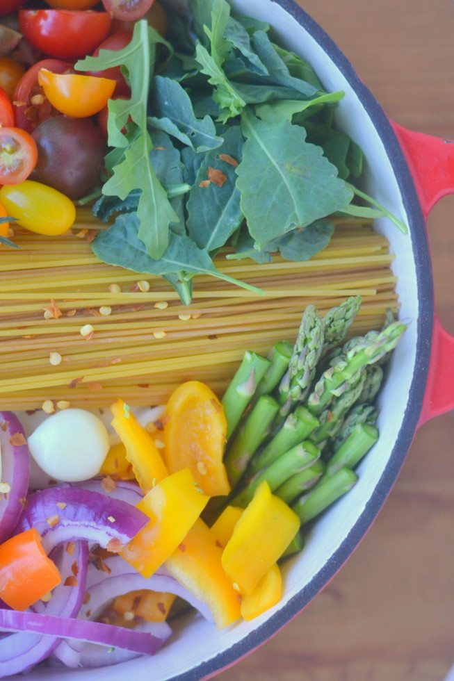 overhead photo of a colorful one pot farmers market pasta in a red cast iron pot