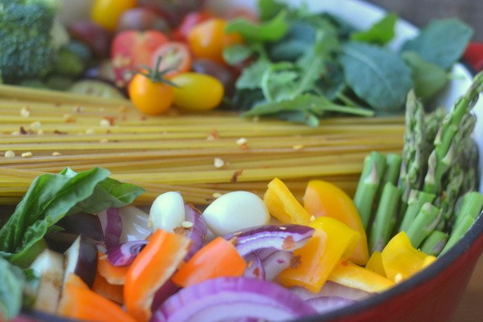 Colorful veggeis and pasta layered in a pot for one pot farmers market pasta
