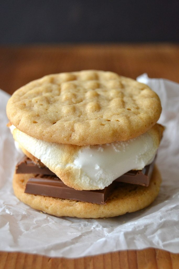 Photo of a peanut butter cookie s'more on a piece of parchment paper.